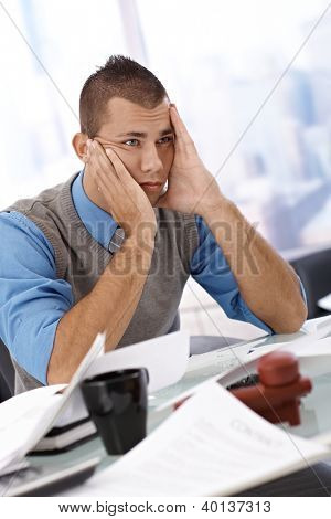 Worried businessman sitting at office desk with face in hands, looking troubled and lost.