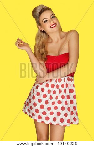 Glamorous blonde retro fashion model in a red polka dot miniskirt with vivid red lipstick and an olden day coiffure posing against a yellow studio background