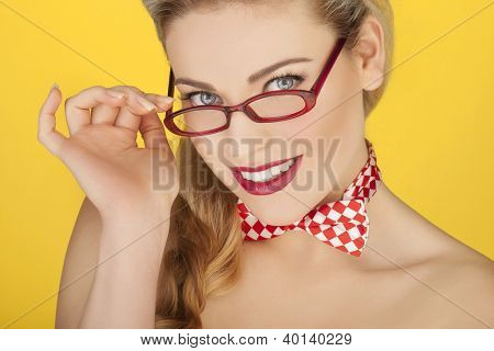 Beautiful glamorous blonde model in stylish modern red glasses and a checked red and white bowtie