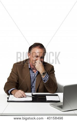 Mature Businessman Looking At Laptop With Hand On Chin