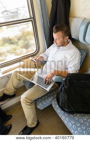 Man texting on phone holding laptop train commuter work journey