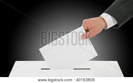 Man hand down ballot in the ballot box