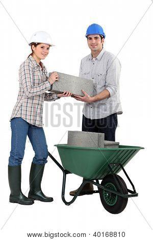 Couple carrying bricks in wheelbarrow
