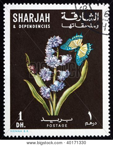 Postage stamp Sharjah 1967 Siberian Squill and Butterfly