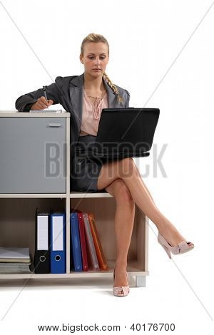 Woman sat with laptop on book case