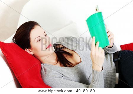 Portrait of a beautiful young woman resting her head on a red pillow, lying on a sofa and reading a book.