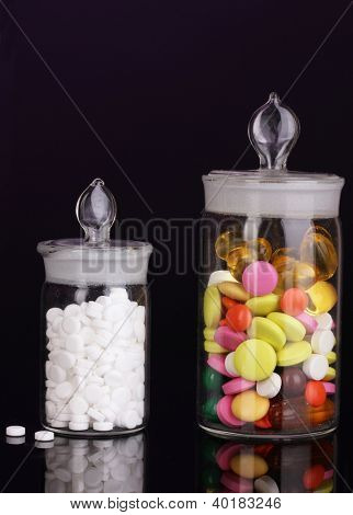 Capsules and pills in receptacles on purple background