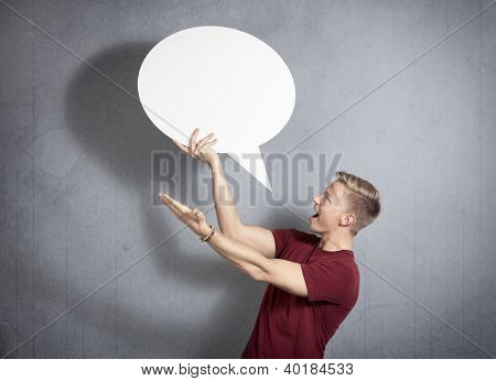 Fantastic news: Amazed handsome man holding white blank speech balloon with space for text isolated on grey background.