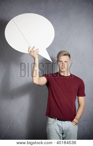 Friendly handsome man holding white empty speech balloon with space for text isolated on grey background.