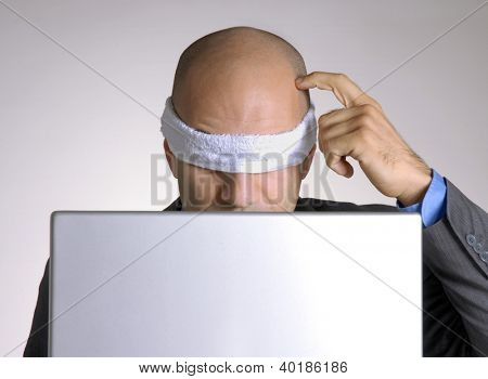 Confused blindfolded bald head man using a computer.
