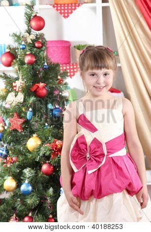 Beautiful little girl in holiday dress in festively decorated room