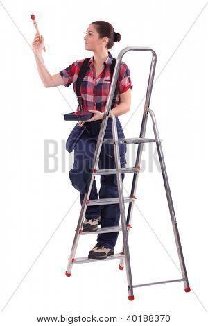 Female decorator climbing a ladder