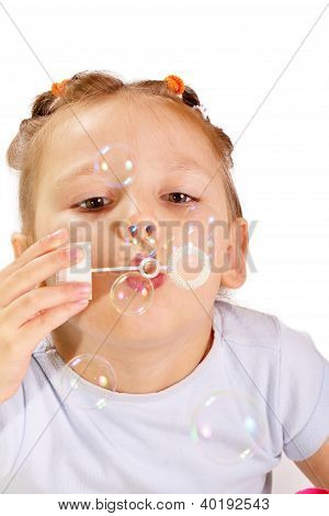 Beautiful Little Girl Blowing Soap Bubbles