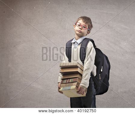 Child with a backpack holding some school books