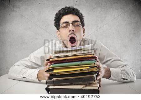 Yawning office worker with a lot of work