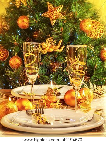 Christmas eve dinner in restaurant, Christmastime table setting over decorated fir tree background, white plates served with knife and fork, two glass for champagne decorated with golden ribbon, party