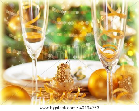 Picture of romantic holiday dinner in restaurant, Christmastime table setting with golden festive decorations, luxury white plate served with glass for champagne, beautiful adorned Christmas tree