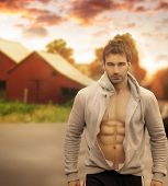 stock photo of red barn  - Beautiful male model with great body in romantic rustic outdoor setting with red barn in background and moody sky above - JPG