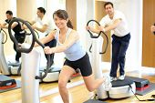 picture of vibrator  - Group of two men and one woman on a vibration massage plate in a gym - JPG