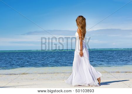 young beautiful woman in wedding dress on tropical beach and water background