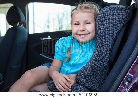 Happy Smiling Young Girl Sitting In Infant Restraint Seat In Car