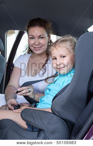 Safety Children Transportation With Car Seat In Vehicle. Mother Fastening Daughter