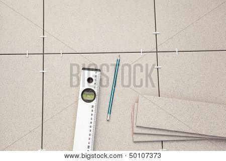 Pre-laying Tiles On Floor With Level Tube And Pencil