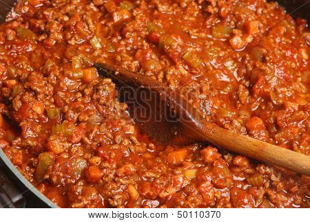 Stirring Spaghetti Bolognese with wooden spoon