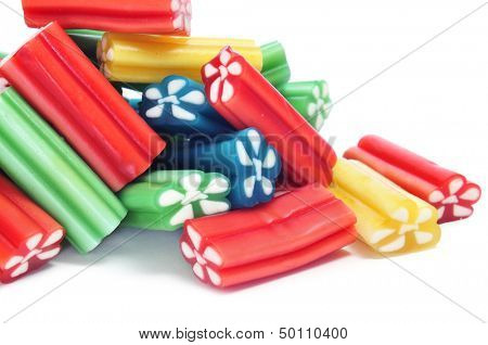 a pile of liquorice candies of different colors on a black background