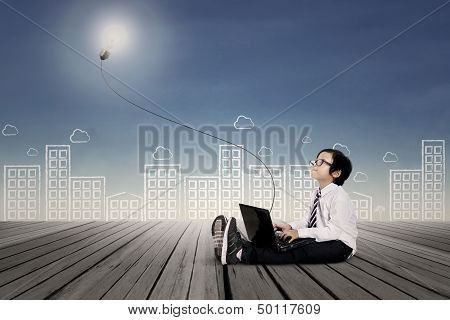 Business Boy Typing On Laptop Under Lit Bulb