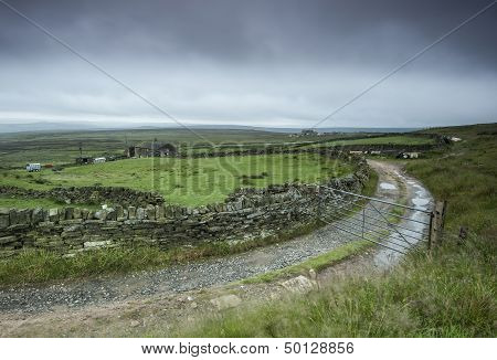 A Yorkshire moorland farmhouse and track photographed on a typically rainy overcast autumn day.