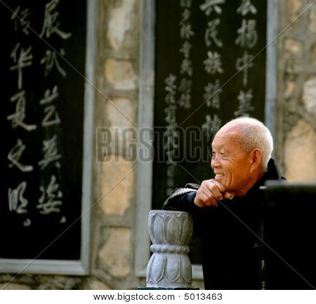 Old Man Smiling And Looking On With Chinese Writing On Wall