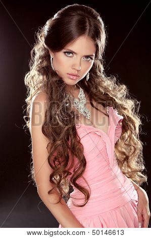 Fashion Photo Of Young Magnificent Woman. Sexy Girl Posing In Pink Dress With Long Curly Hair Isolat