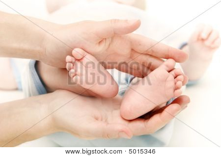 Baby's Feet In Parent's Hands Over White