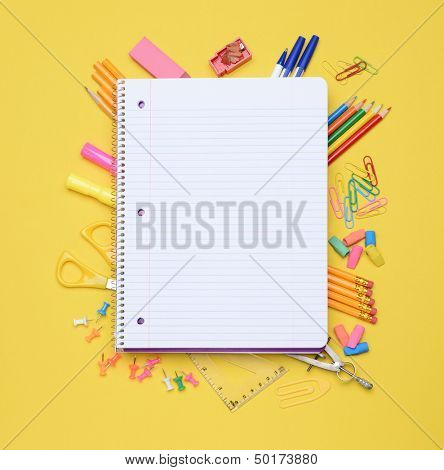 An open spiral notebook laying on assorted school supplies. Back to School concept. Equipment includes, pens, pencils, erasers, compass, scissors, paper clips and more.
