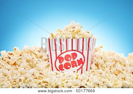 Popcorn in classic box overflowing with freshly popped corn against a blue background