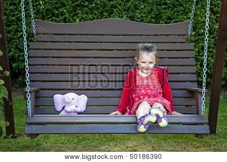 Little Girl On Swing With Teddy Bear