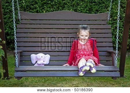 Little Girl On Swing With Teddy Bear