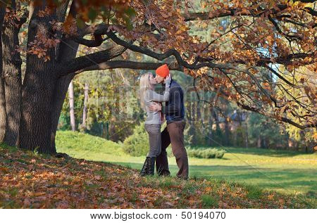 Happy couple kissing in autumn forest