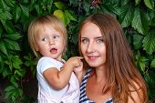 foto of gleaning  - Mother holds daughter on hands on a background of city park - JPG