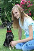 picture of miniature pinscher  - Smiling attractive young teenage girl sitting on green grass with her small dog a miniature pinscher - JPG