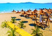 stock photo of sunny beach  - Straw umbrellas on beautiful sunny beach in Bulgaria - JPG