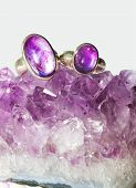 stock photo of metaphysical  - Amethyst crystals forming part of a geode with two rings having polished amethyst cabochons a purple form of quartz it is used in crystal healing as a treatment against addiction  - JPG
