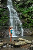 image of one piece swimsuit  - Beautiful slim fitness model posing sexy in front of waterfalls wearing one - JPG