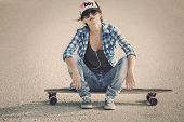 stock photo of skateboarding  - Beautiful young woman sitting over a skateboard - JPG