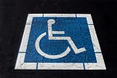 foto of handicap  - Universal Worn Handicapped Symbol Painted on Ashpalt - JPG
