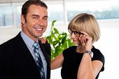 picture of flirtatious  - Flirtatious secretary resting her one hand on bosses shoulder and adjusting glasses with other - JPG