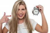 image of time-piece  - Portrait of a long haired teen girl pointing towards old fashioned time piece - JPG