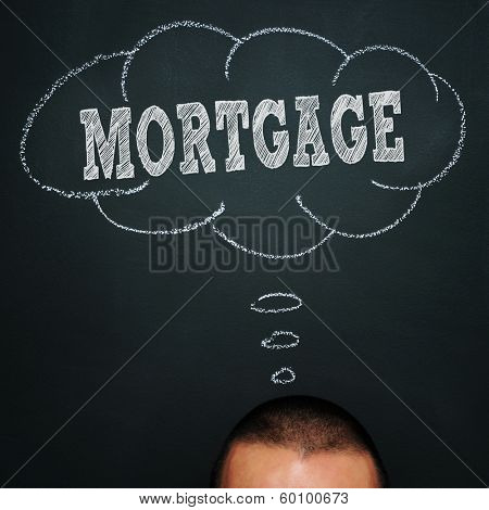 a man over a blackboard with a thought bubble drawn in it and the word mortgage, depicting the idea of being worried about the mortgage