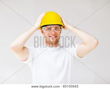 building, developing, consrtuction and architecture concept - picture of male builder in safety glasses and yellow helmet